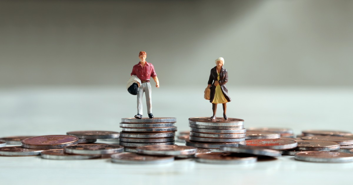 Miniature male and female figurines standing on equal piles of coins