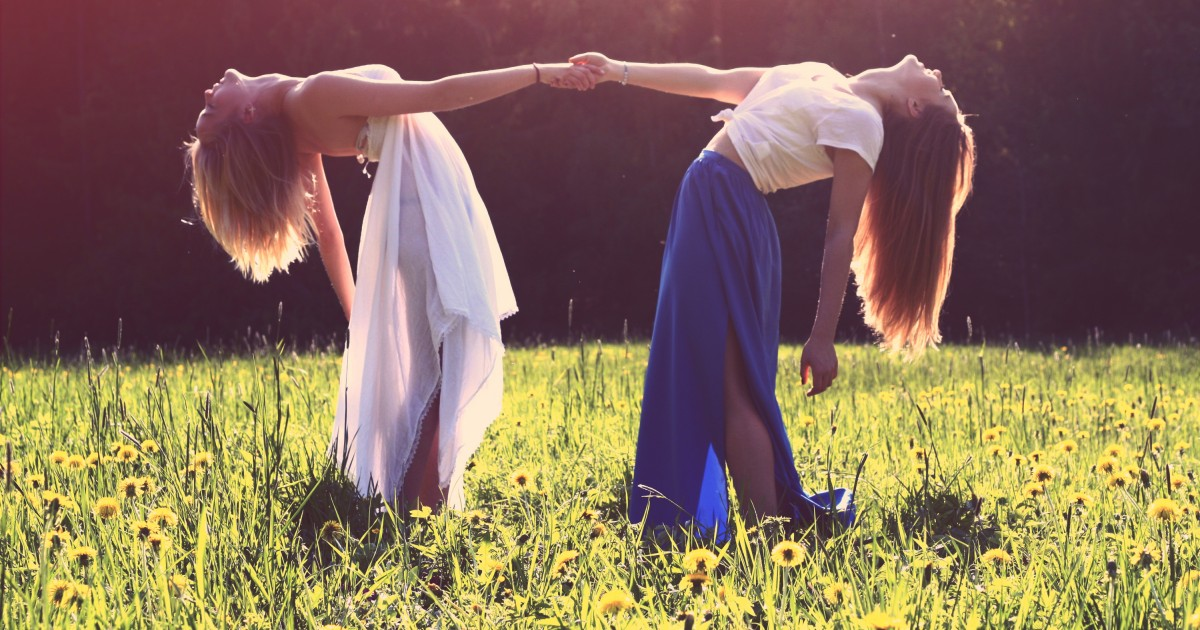 Two young girls leaning all the way back while holding hands in a field with sunlight
