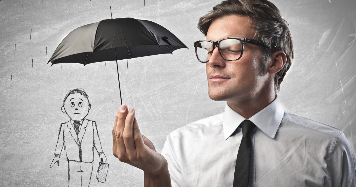 Man holding an amusingly small umbrella over a drawing of a man, illustrating insurance coverage